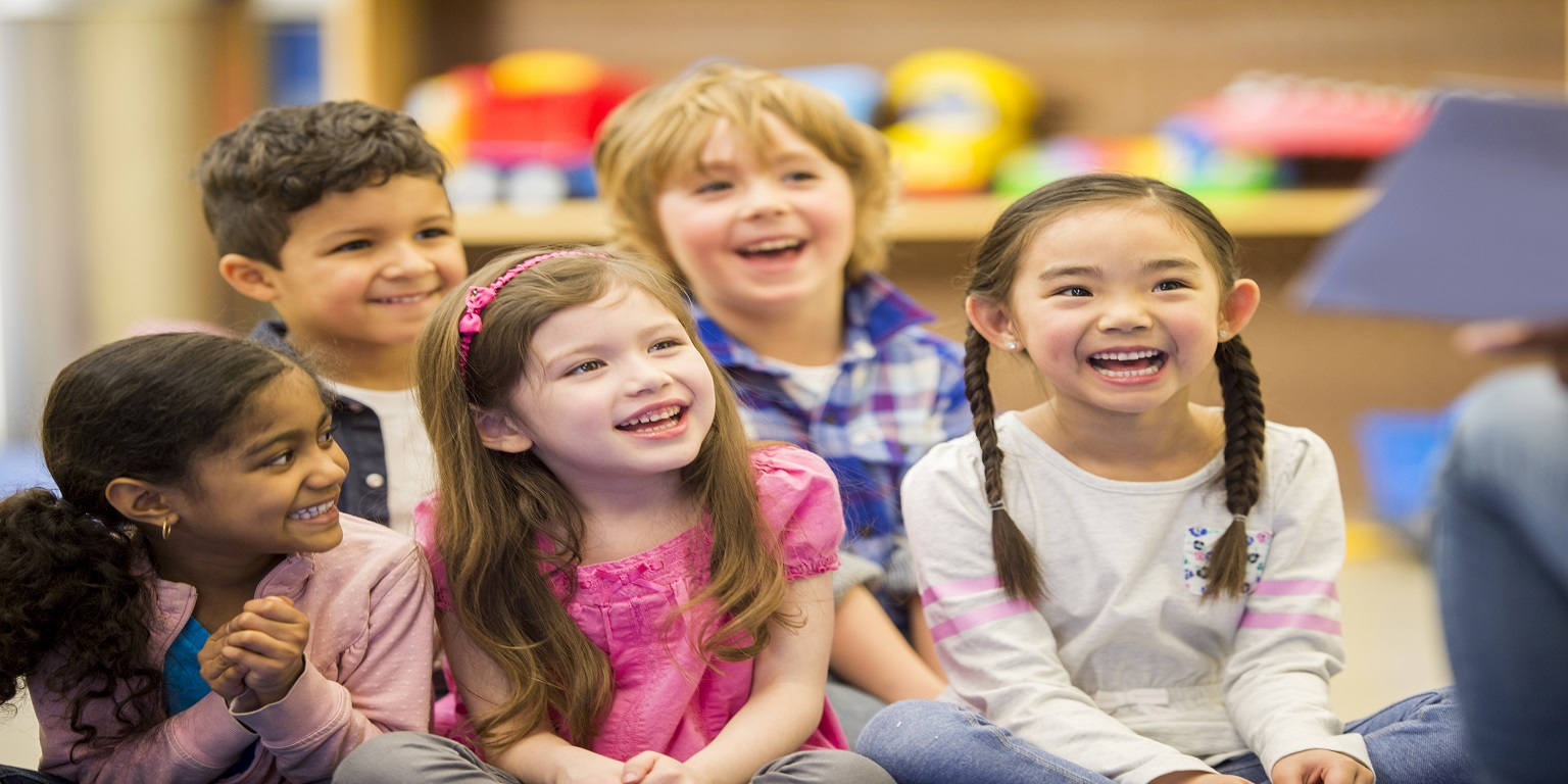 group of  children smiling as they listen to a story