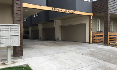 Image of garage entrance to slot home development, which creates a wide curb-cut on sidewalk