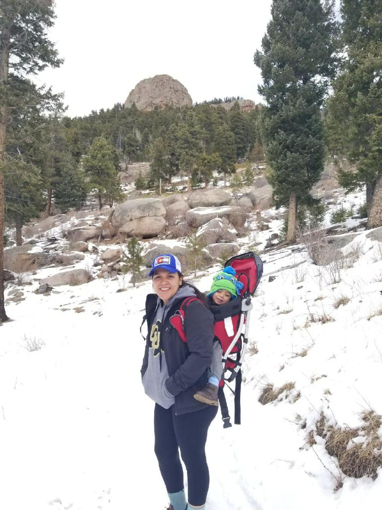 Sweaty person with child in backpack carrier on snow covered mountain trail.