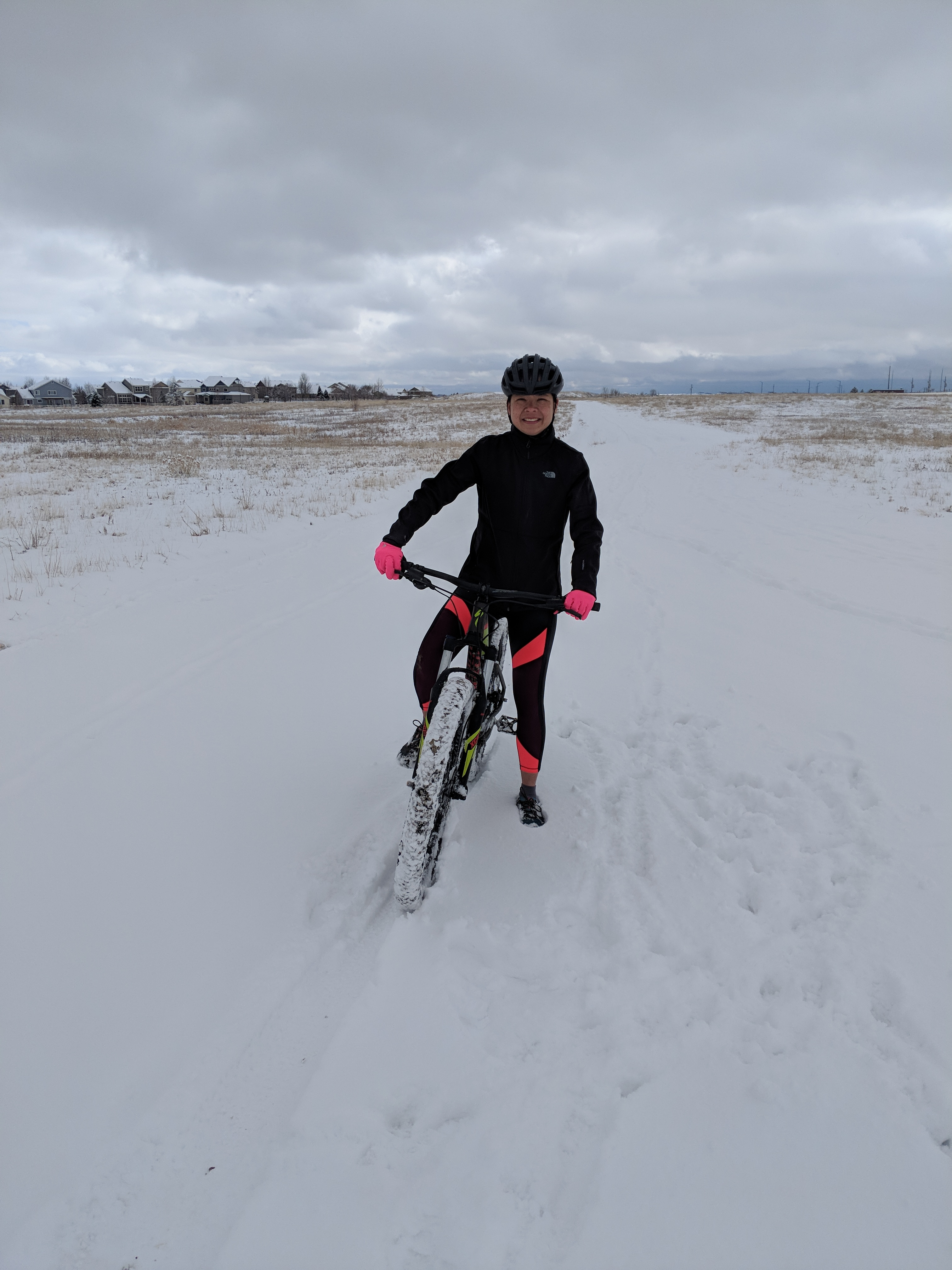Sweaty person riding bike in the snow.