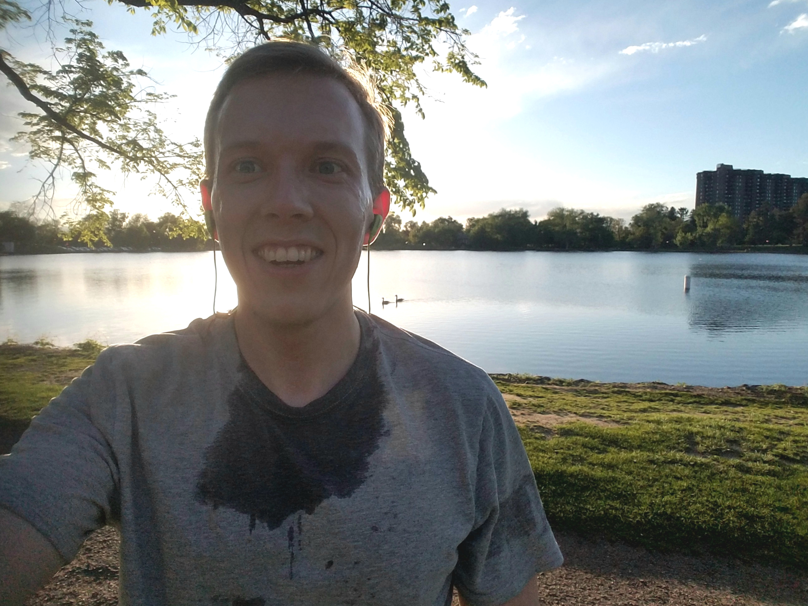 Sweaty person with earbuds in, standing in front of Denver lake.