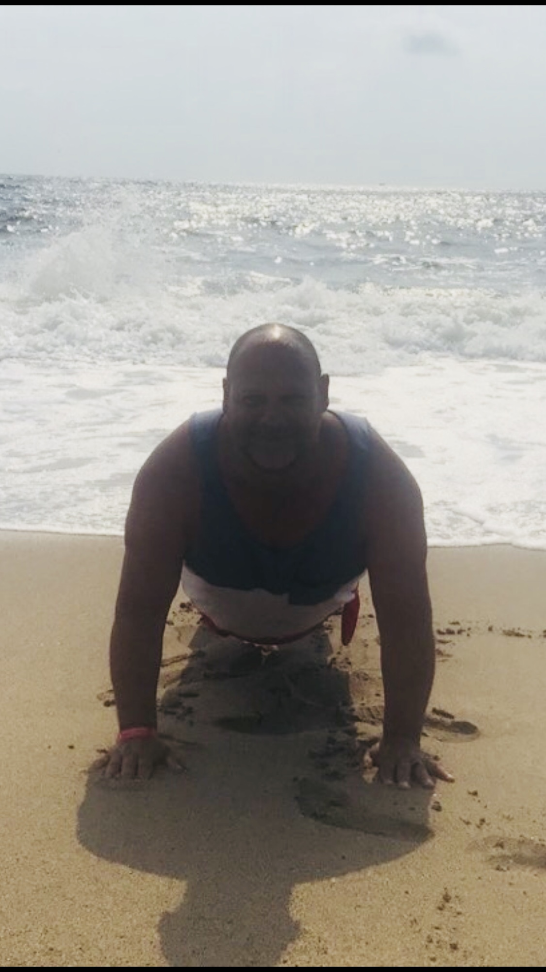 Sweaty person doing push ups on the beach with ocean in background.