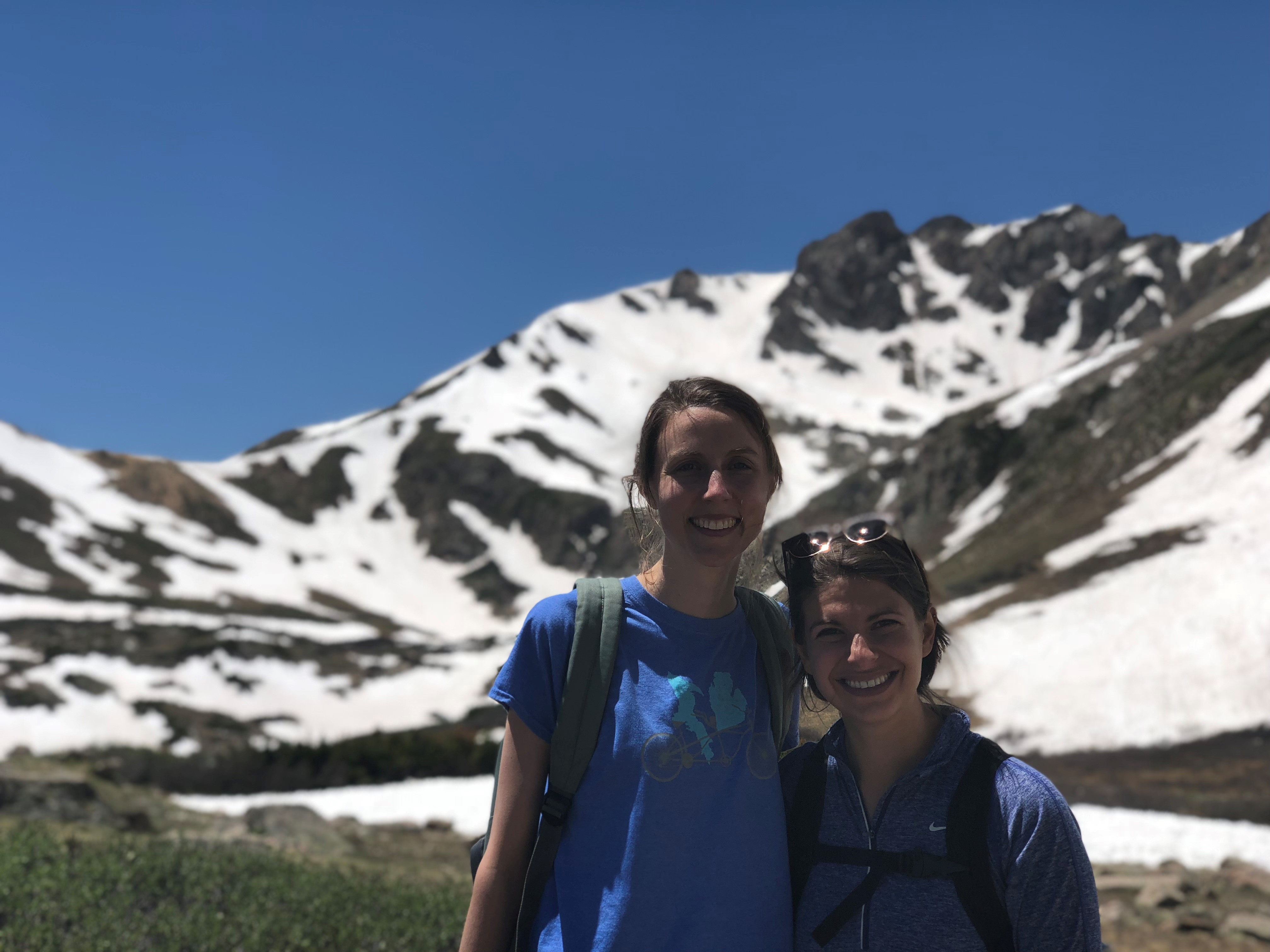 Two sweaty people on mountain hike above tree line.
