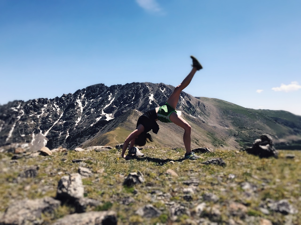 Sweaty person doing yoga above treeline.