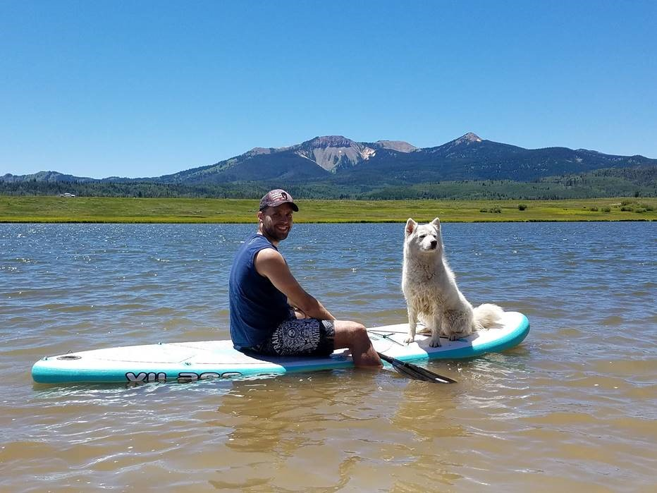 Sweaty person on paddle board with sweaty dog.