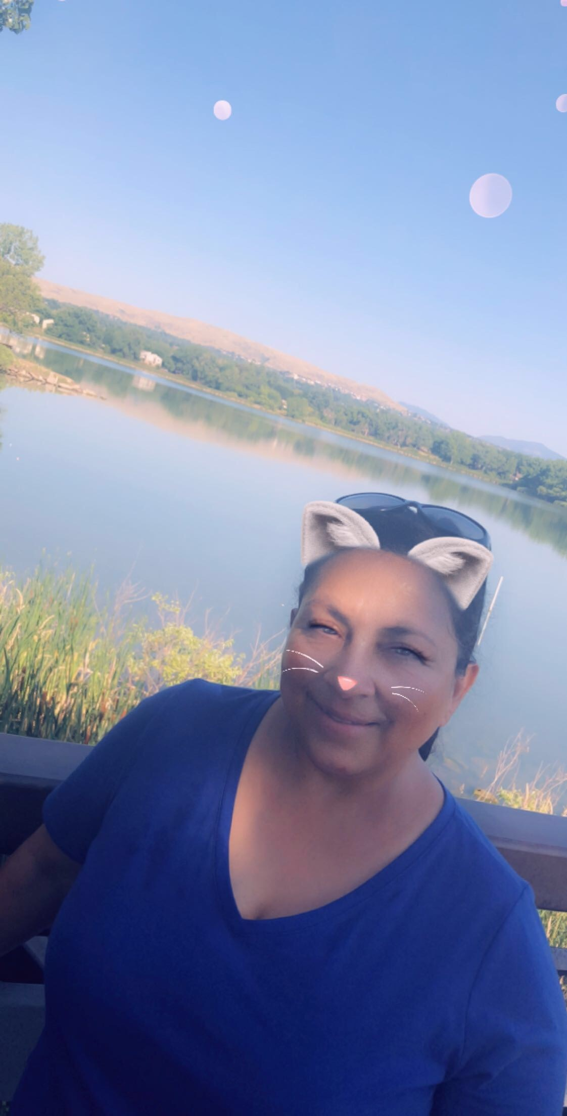 Sweaty person with cat ears and whiskers in front of lake.
