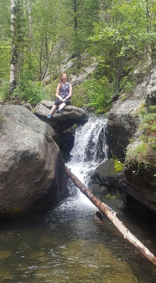Sweaty person sitting on rock by water fall.