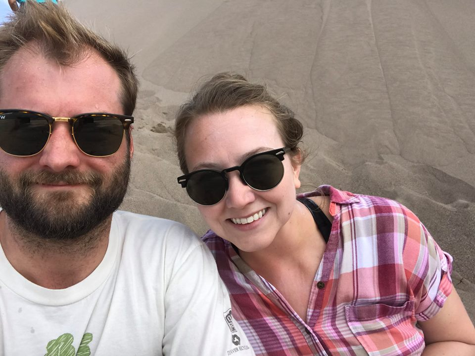 Two sweaty people at sand dunes.
