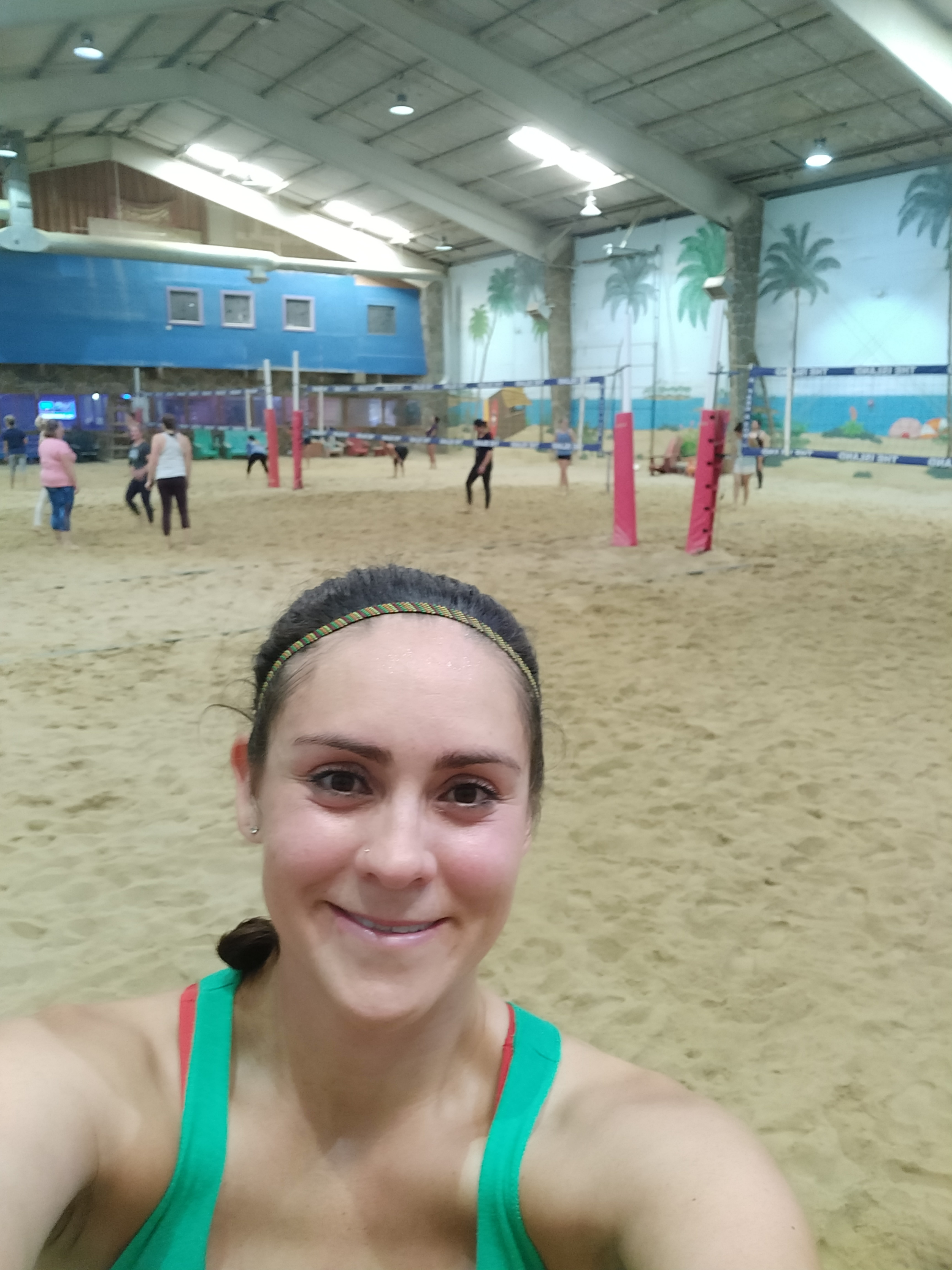 Sweaty person playing indoor beach volleyball.