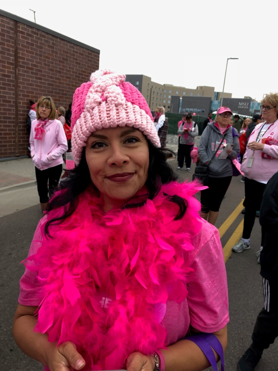 Sweaty person wearing pink Breast Cancer awareness beanie and pink feather boa.