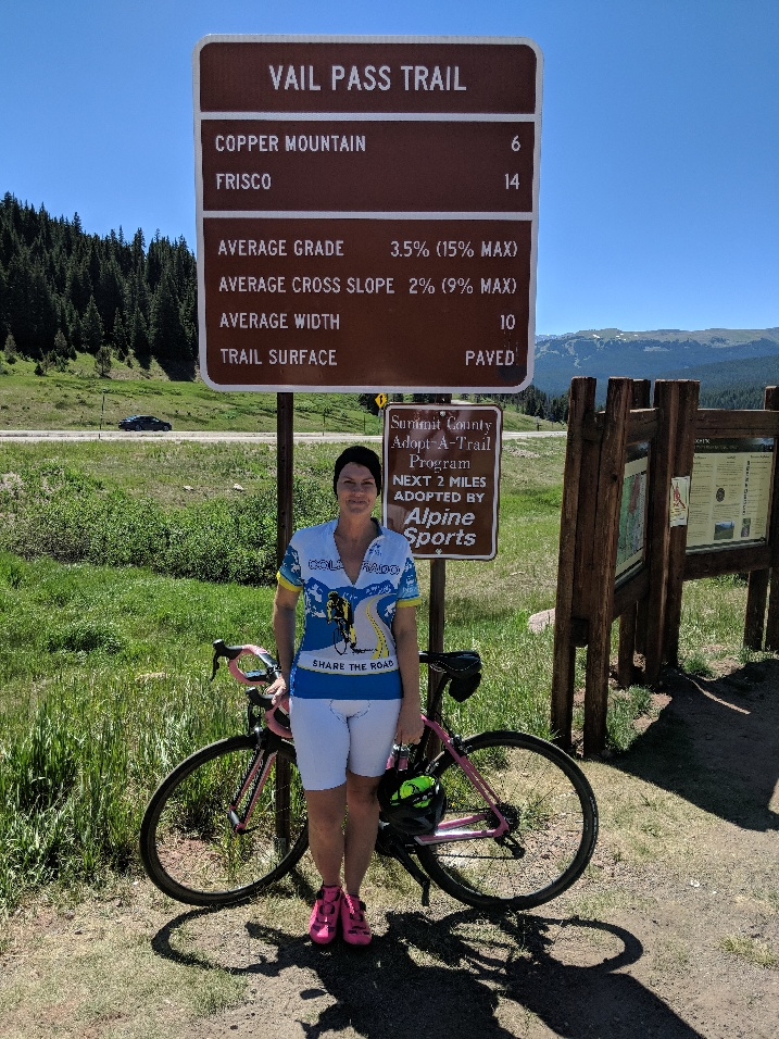 Sweaty person standing with bike on Vail Pass Trail.