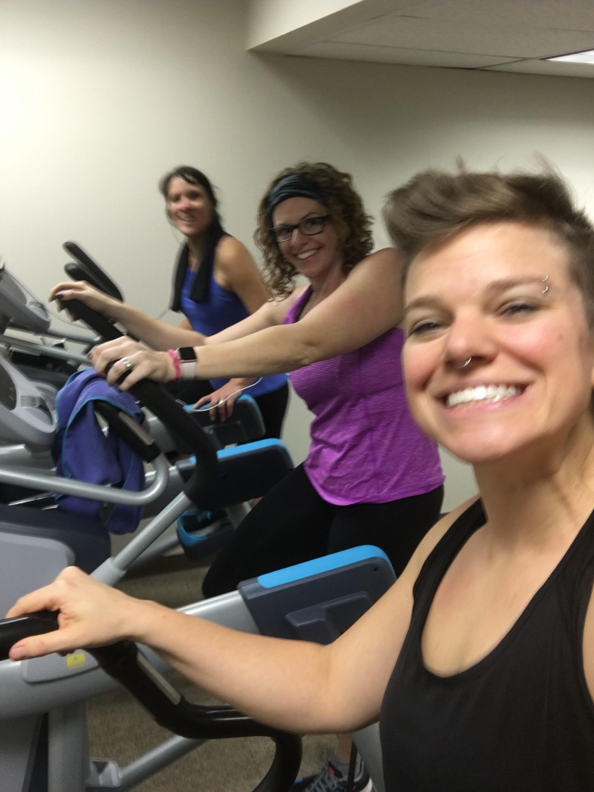 Sweaty people working out on ellipticals.
