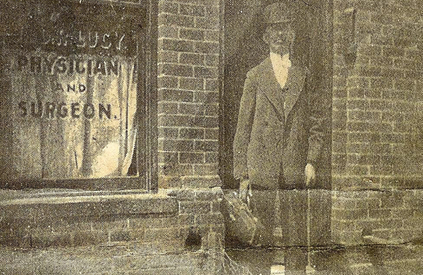 Newspaper clipping of Dr. Lucy, a former councnil member, standing outside his medical practice.