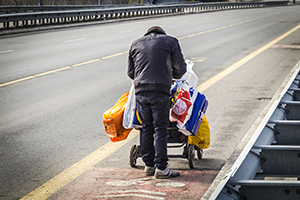 Homeless man pushing a cart with his belongings in it