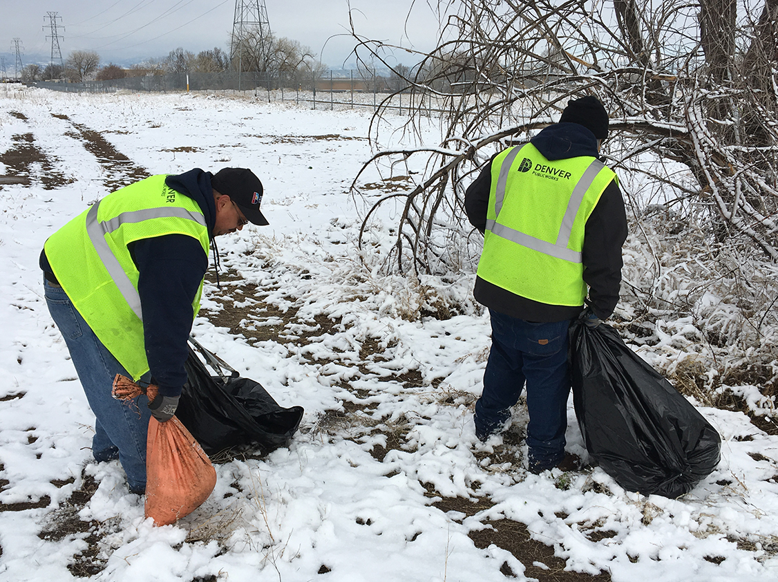 crew members in safety vests carring bags of trash in snowy park area