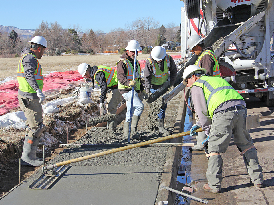 crews smoothing out new sidewalks as part of DOTI