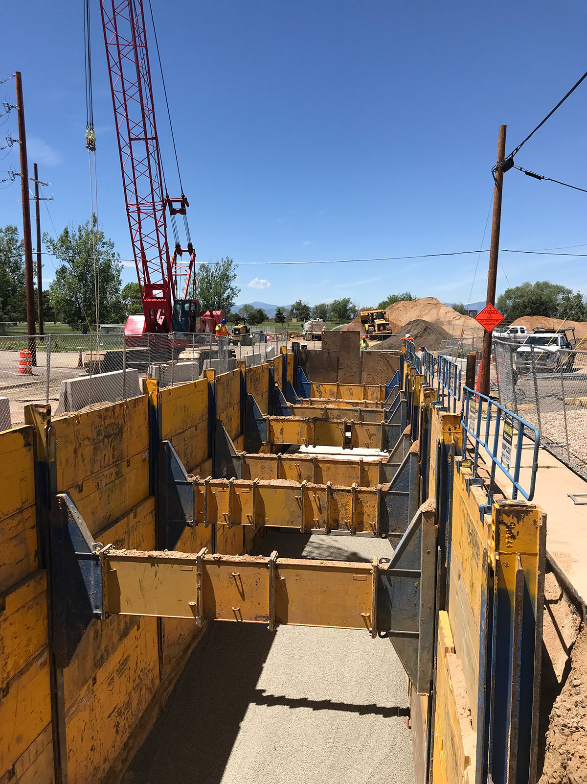 construction site with large box culvert structures in deep trench along roadway