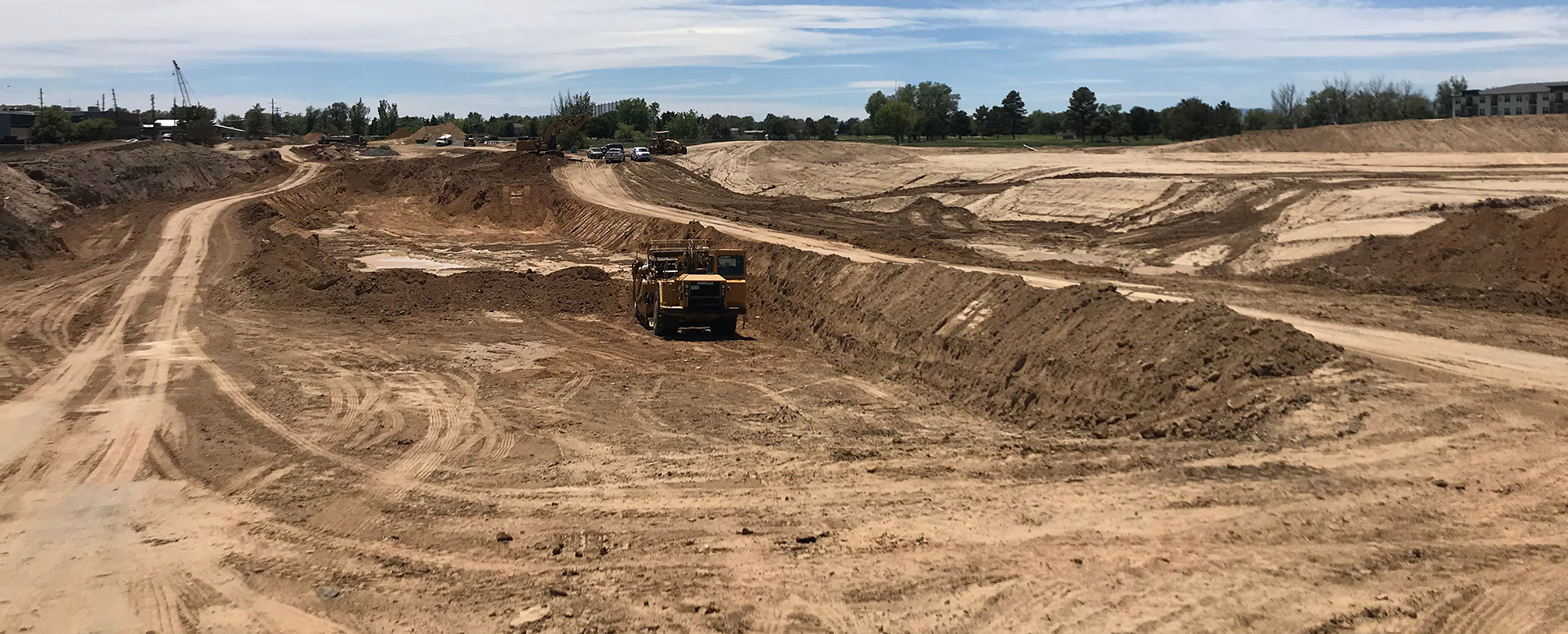 dirt construction zone with golf course in background