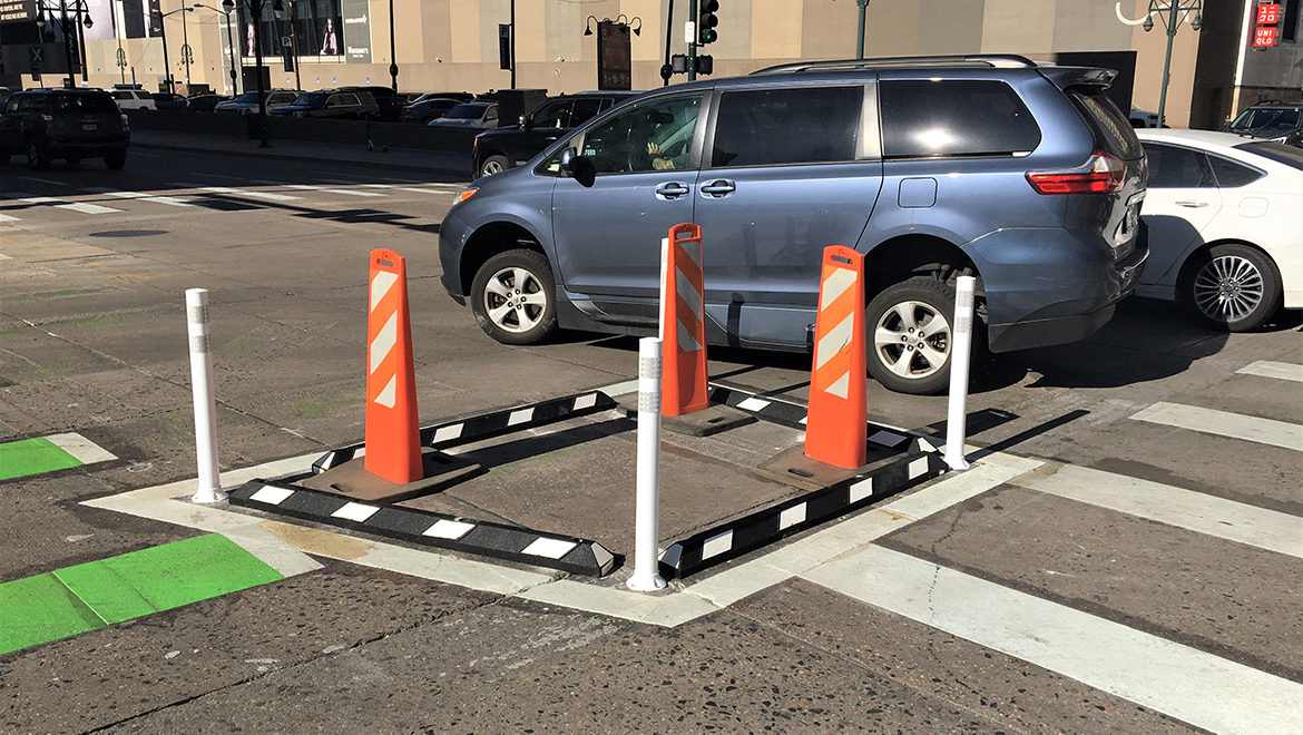 car turns around newly installed bollards and curbs at 15th Street intersection next to protected bike lane
