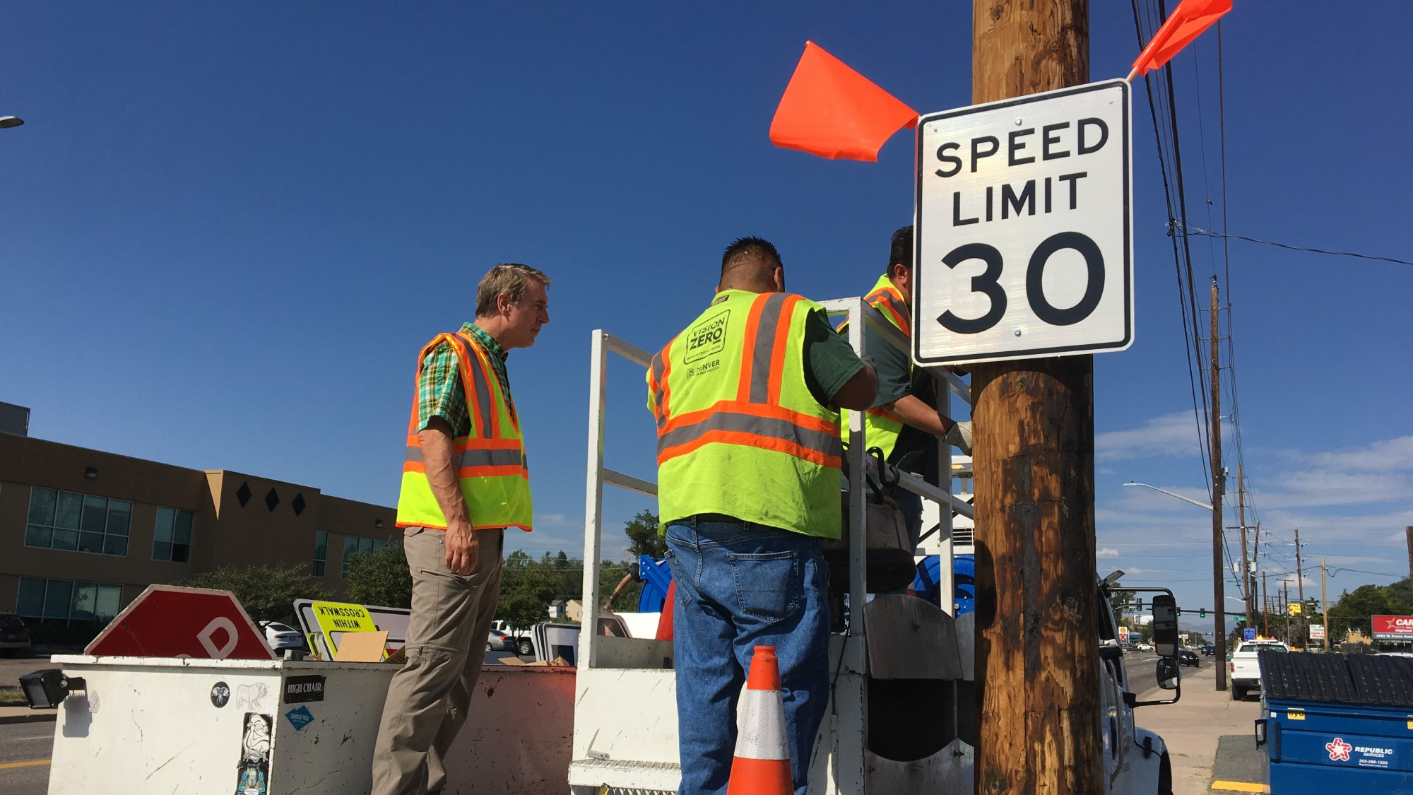 crews install 30 mile per hour speed limit signs and flags to alert drivers