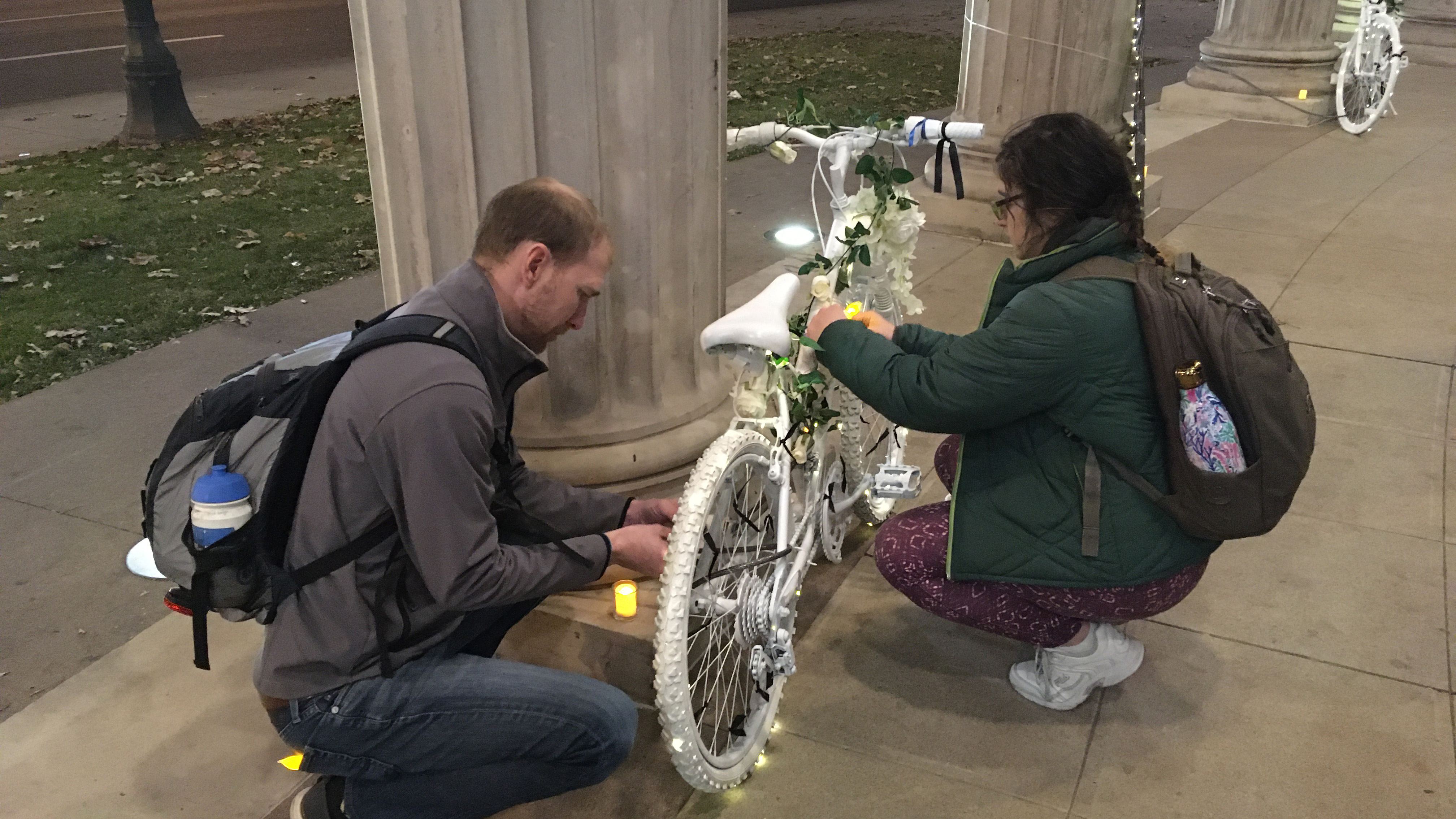 two people affix lights to a white painted ghost bike to commemorate a person killed in a traffic crash