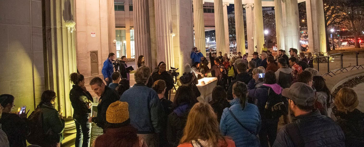 crowd of people at Civic Center plaza evening vigil looking at candles on table representing people killed in traffic crashes since 2016
