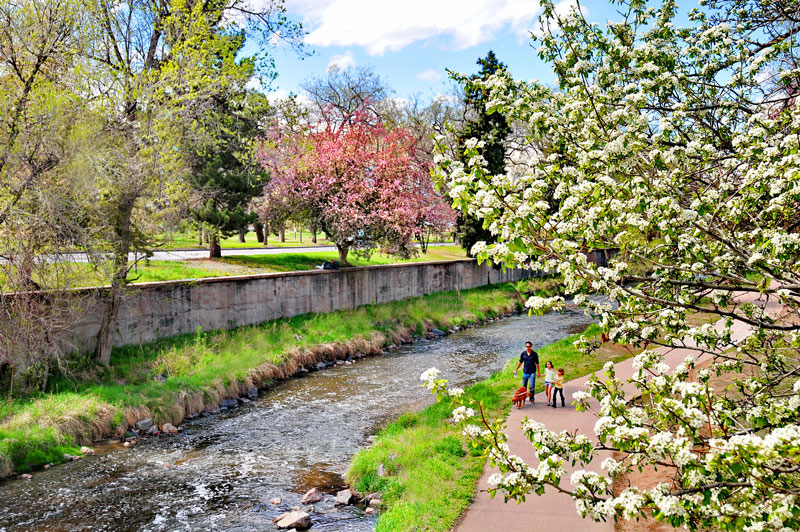 pedestrians walk next to Cherry Creek in spring