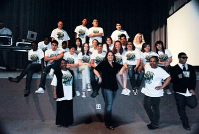 volunteers and students posing on stage
