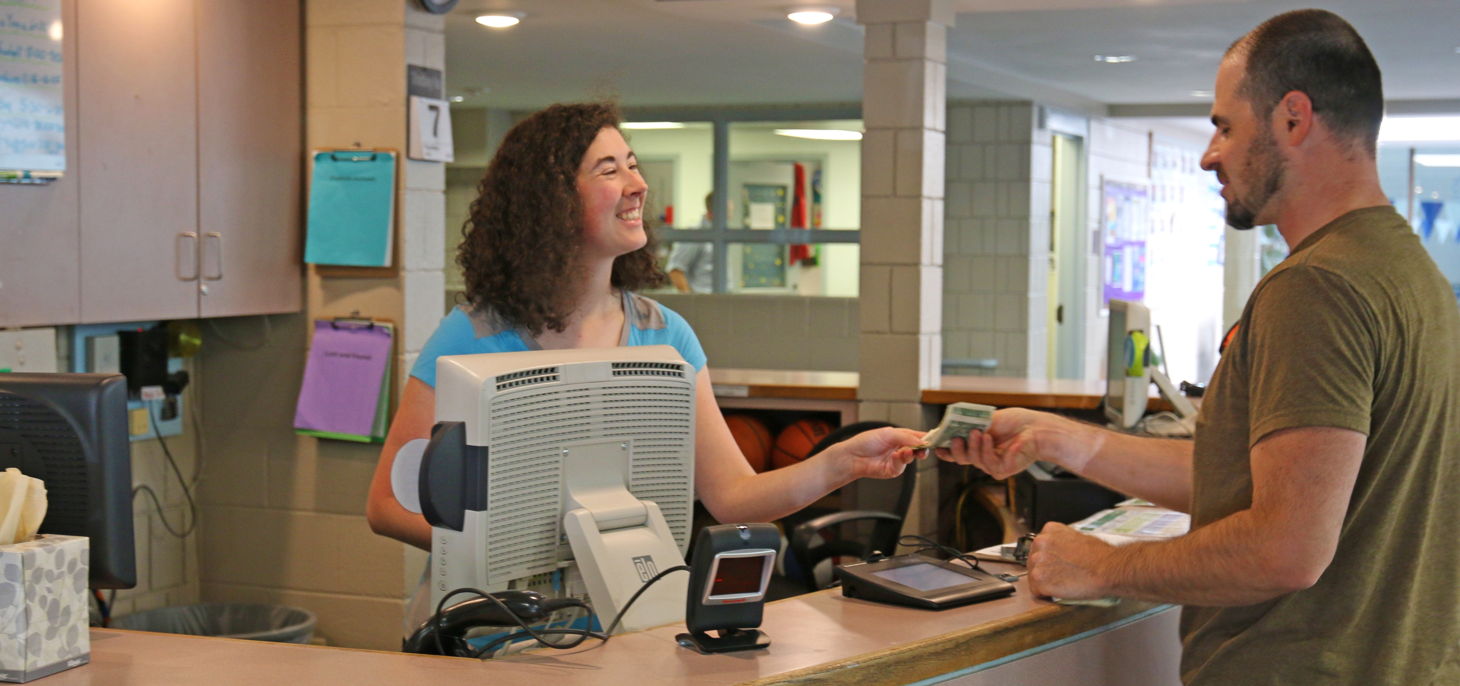 photo of a front desk parks and recreation staff assisting a customer