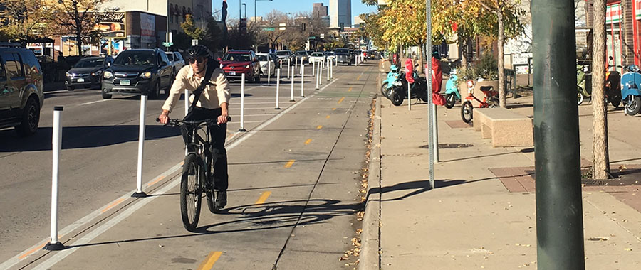 A man rides his bike in the protected bike lane along south Broadway.