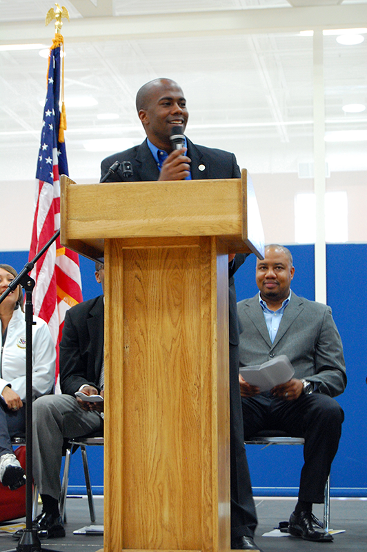 Photo of Christopher Herndon speaking at a podium for a local Denver event