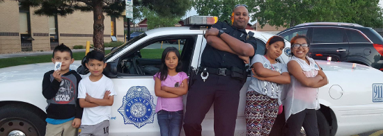 cop posing with children near cop car