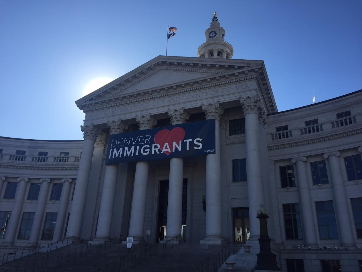 image of city and county building in denver with Denver Loves Immigrants banner