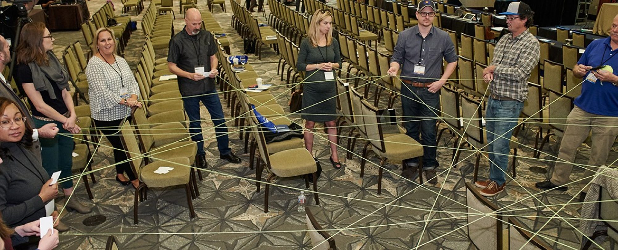 Group of individuals working on a group project with string.