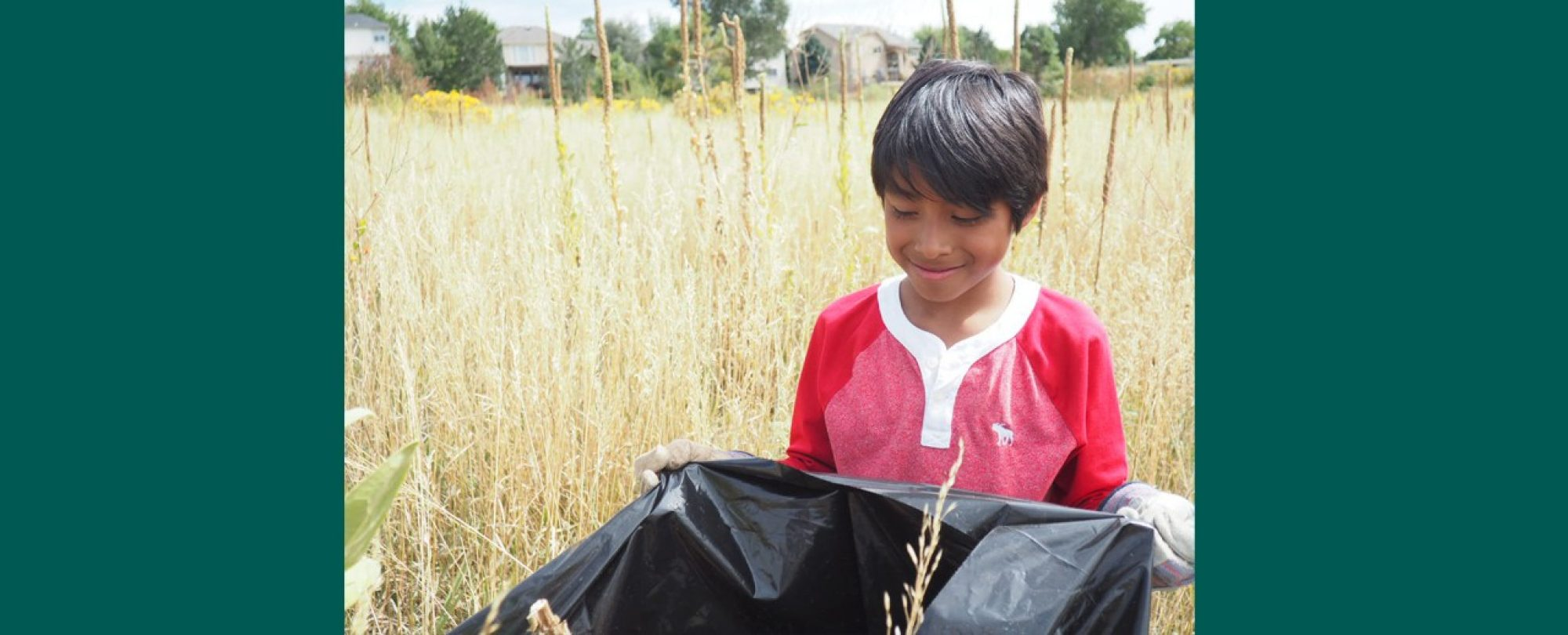 Boy picks up trash as part of an outdoor volunteer project.