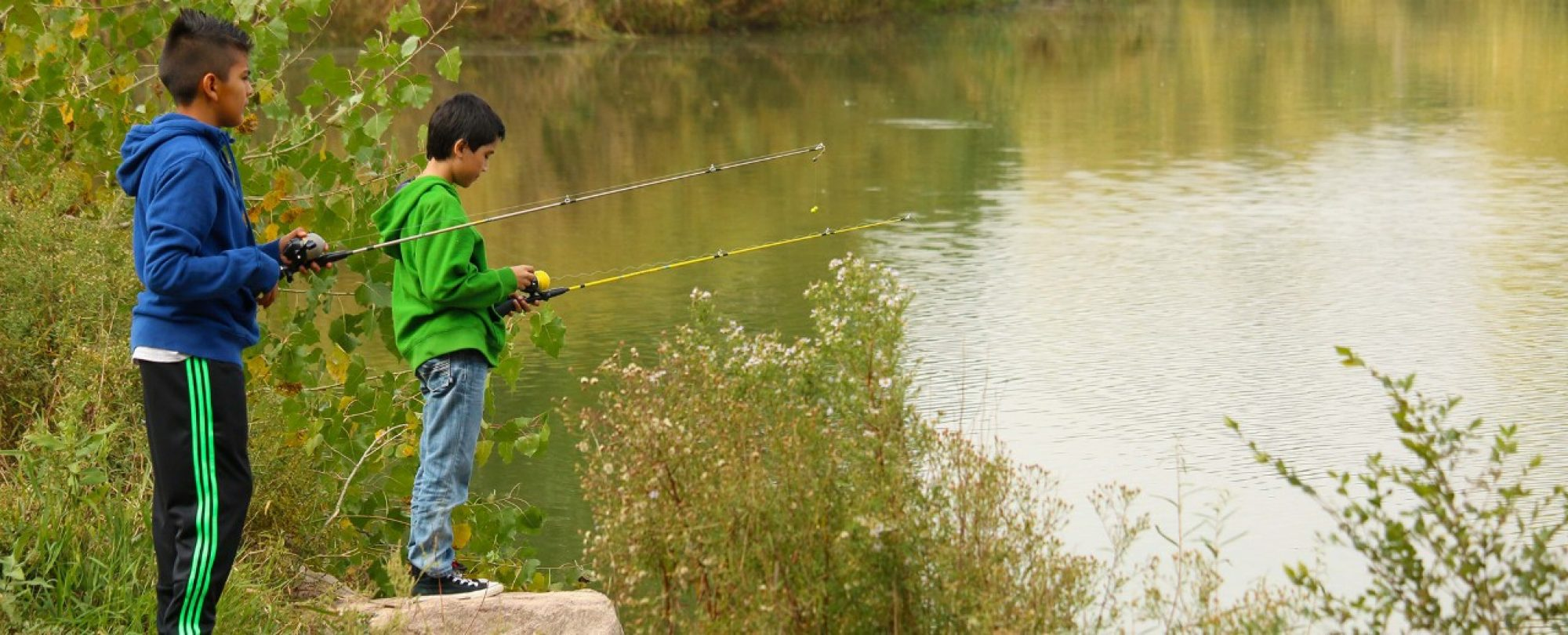 Park Ranger Fishing Program, Image shows to young kids fishing in a water source.