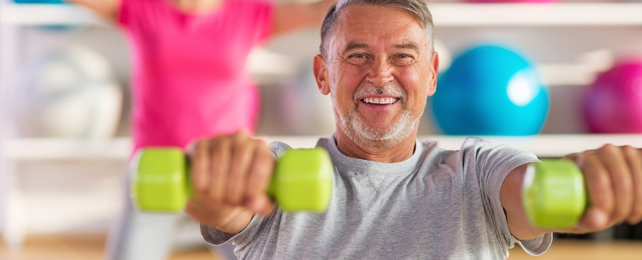 Elderly Man Holding Green Weights in Front of him