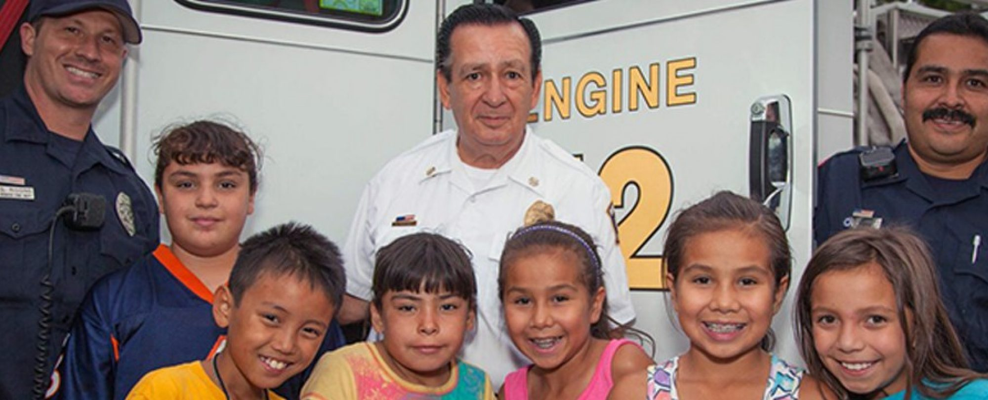group of children posing with firefighters