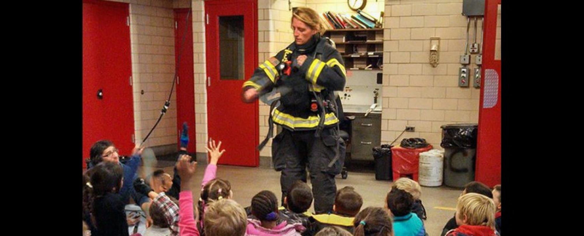 firefighter giving equipment demonstration to children