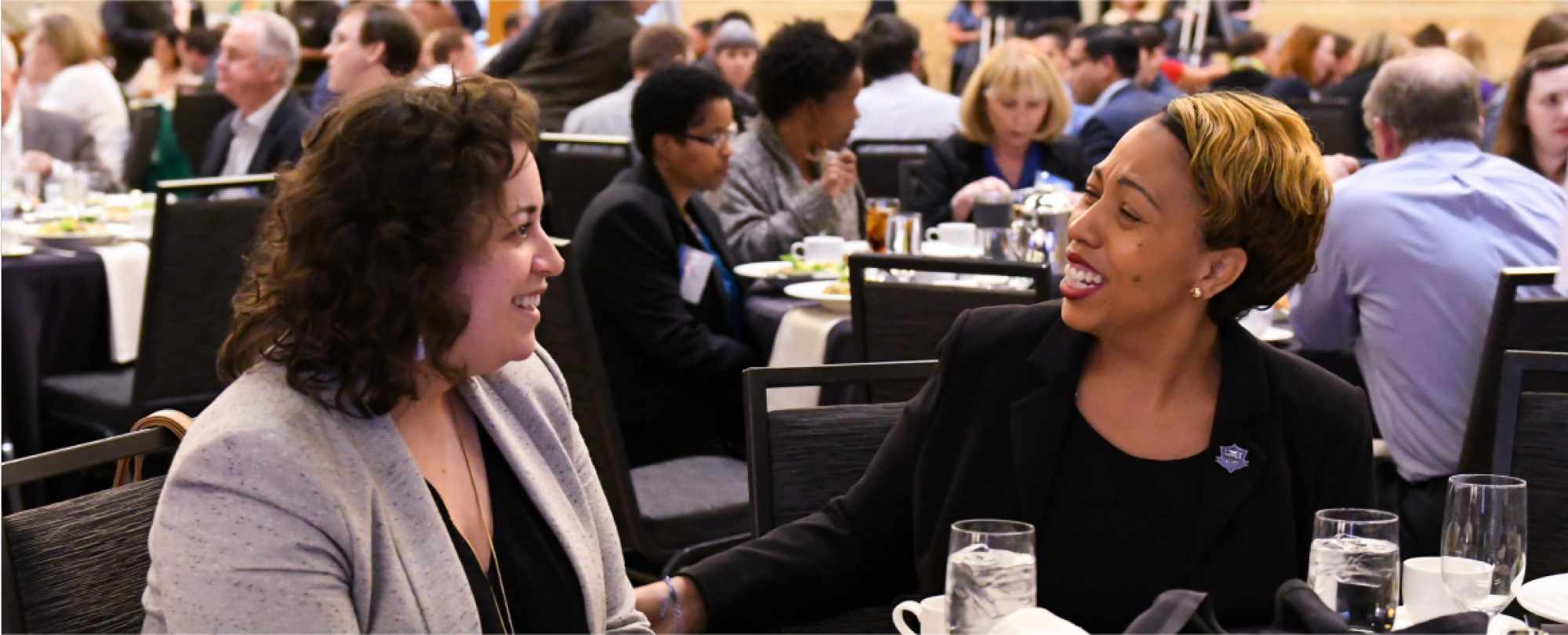 Two people having am enjoyable conversation during the 2019 Denver Housing Forum lunch