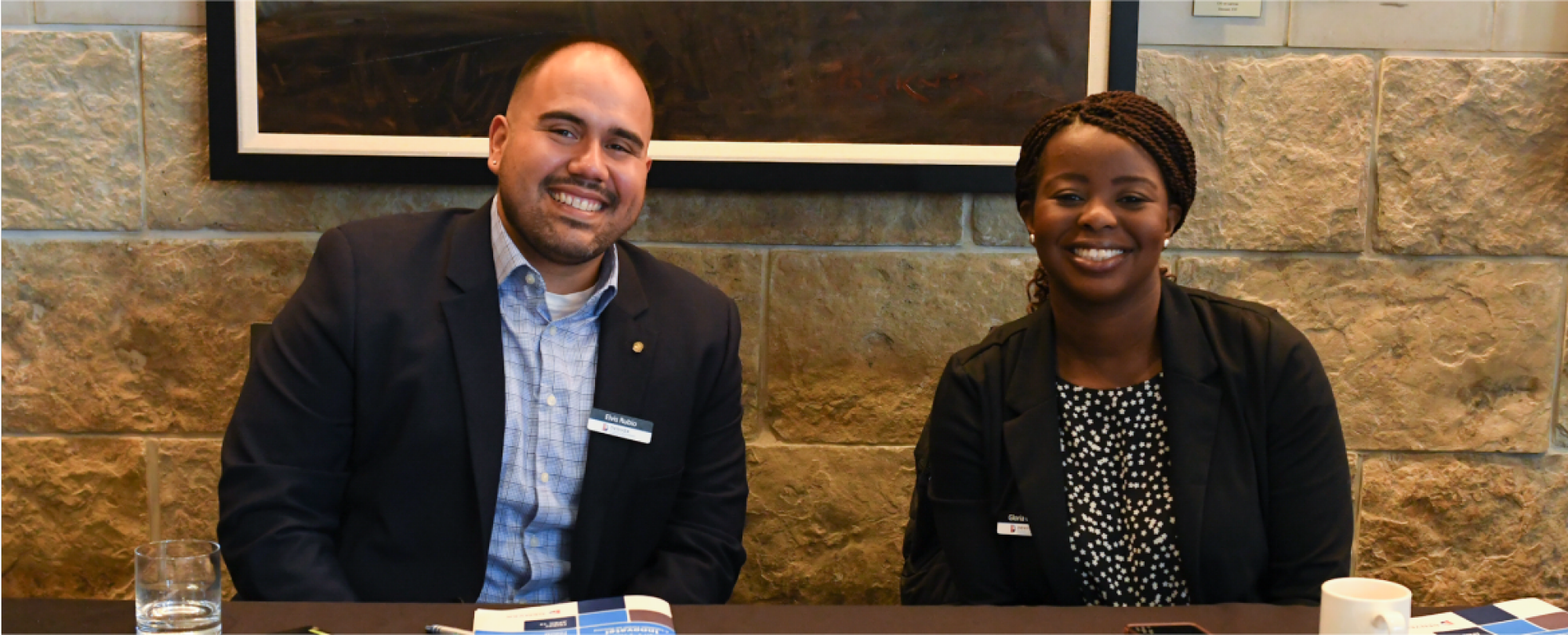Two people posing together at a 2019 Denver Housing Forum table