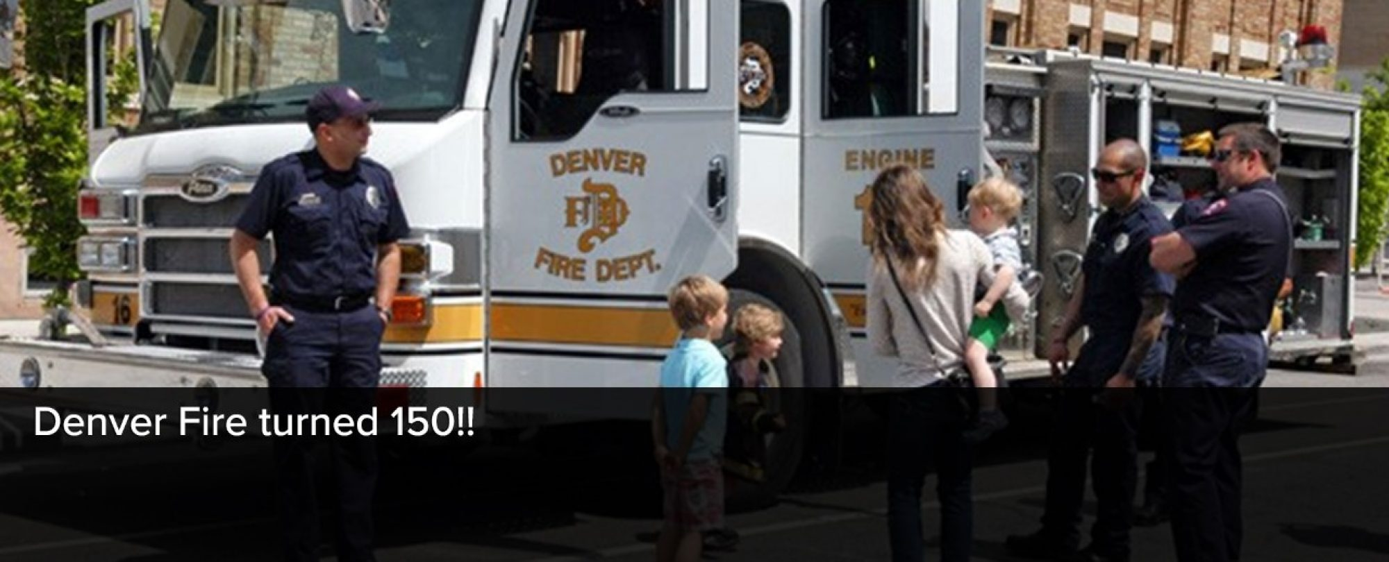 Photo of Denver Firefighters showing families a tour of one of their Fire trucks. Denver Fire Department turned 150 in 2016.