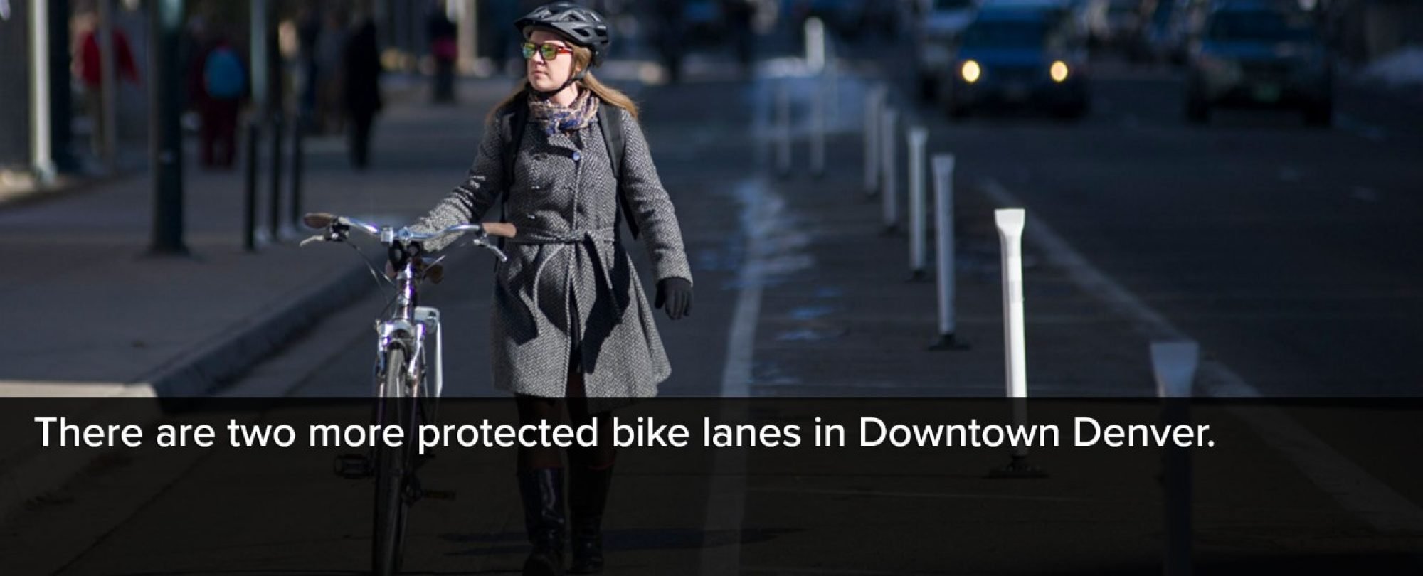 Photo of woman walking her bike along one of the three new protected bike lanes in Downtown Denver