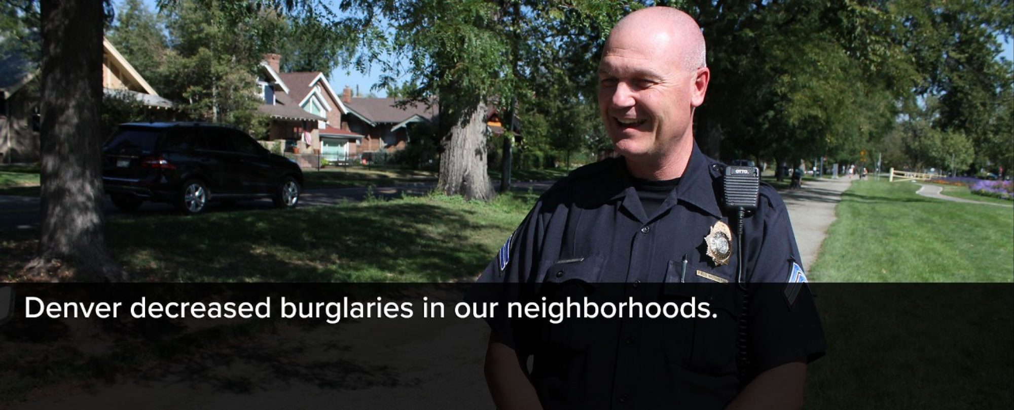Photo of Denver Police officer in local Denver neighborhood. Denver decreased burglaries in Denver neighborhoods over the year