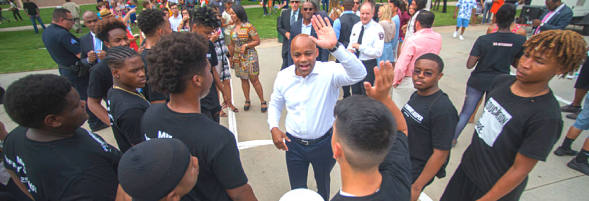 Photo of Mayor Hancock with group of young men and the text Youth Violence Prevention: Intervene, Suppress, Prevent""