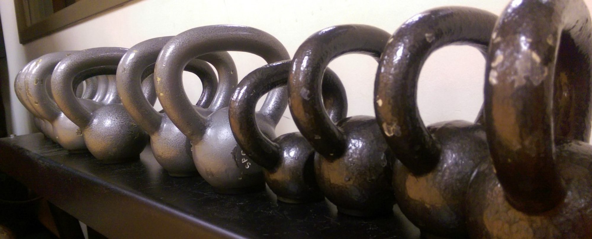 photo of dumb bells in gym rack