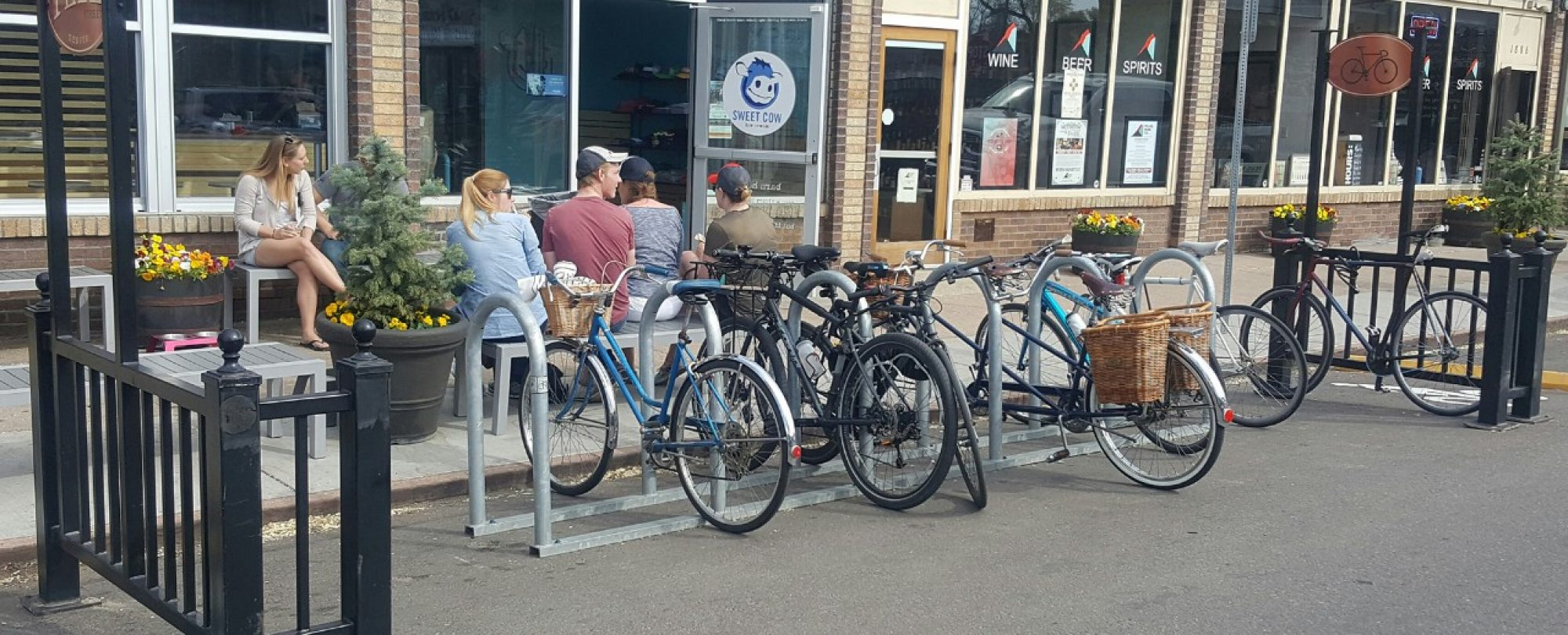 bike corral with parked bicycles outside of ice cream shop, with patrons using sidewalk seating