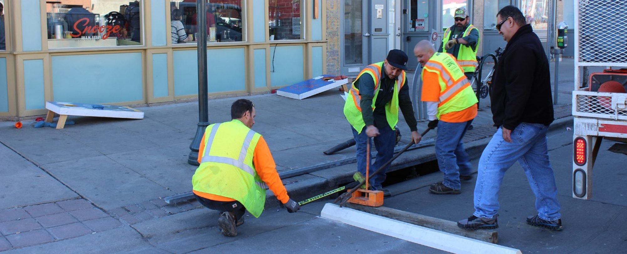 crew in safety gear installing bike parking outside Snooze restaurant