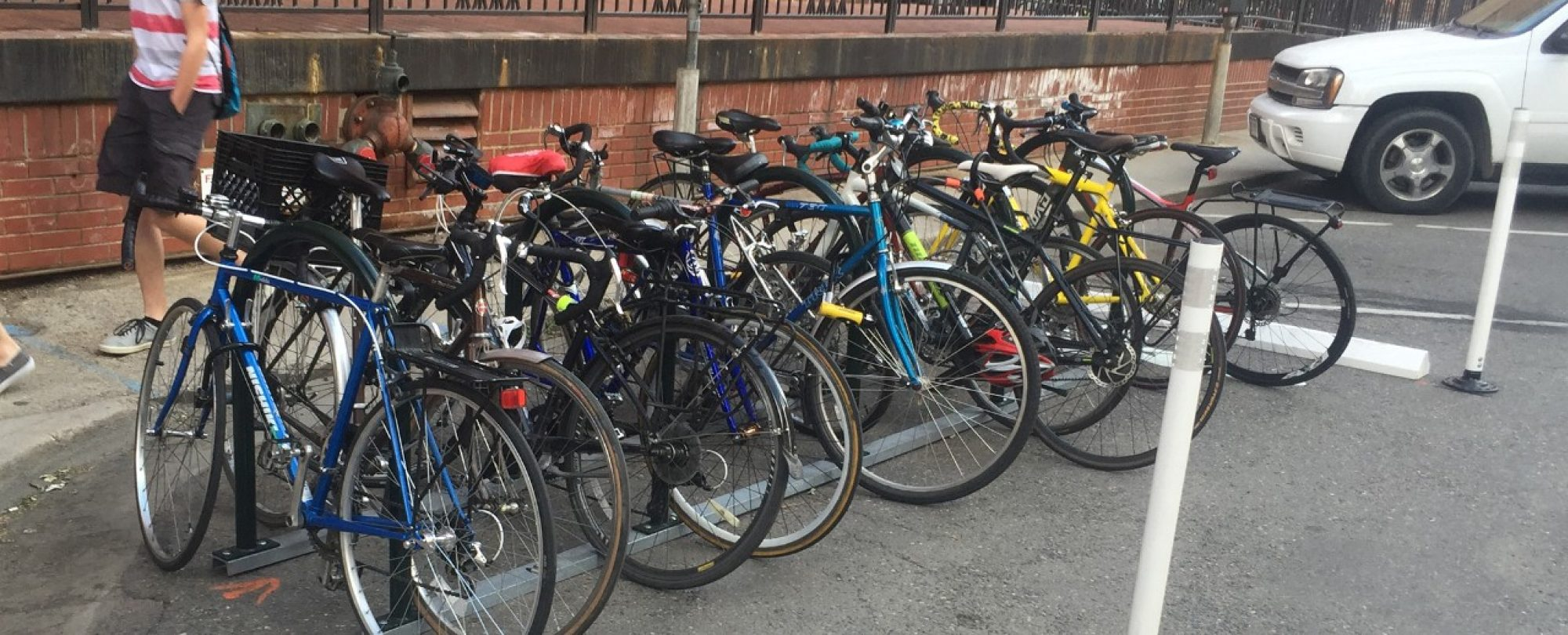 bikes in corral next to vehicle parking spaces