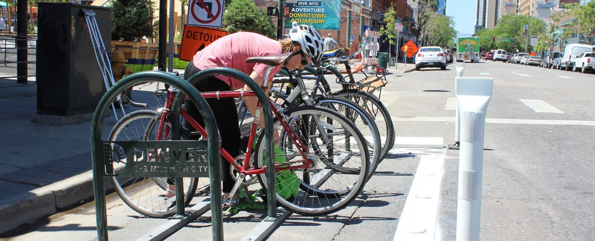 rider in helmet unlocking bike at Denver branded bike parking rack